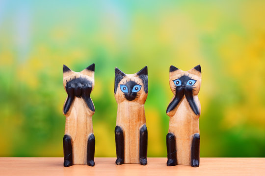 Chinese cats figures Nothing see, Nothing hear, Nothing talk on the table on green background