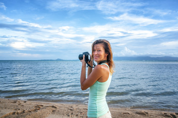 Young beautiful woman photographer with camera in hands on the seashore