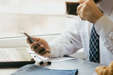 Young businessman with smartphone in cafe