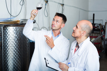 Two winery workers standing with glass of wine