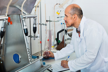 Mature man working on quality of products in winery lab