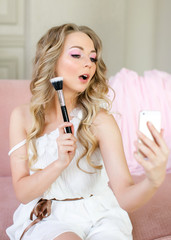 Blonde girl with a make-up brush and a phone shoots a photo