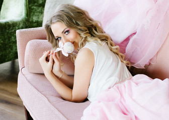 Stylish blonde in pink is lying on the couch with a cake-pop in her hands. Professional makeup