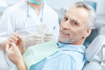Mature patient looking at tooth sample while visiting dentist