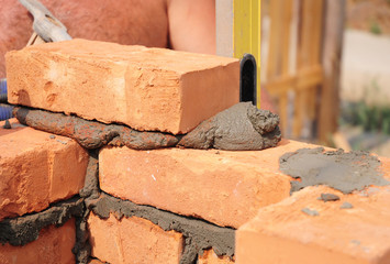 Bricklaying, Brickwork.Bricklayer worker installing red blocks and caulking brick masonry joints exterior brick house wall with trowel putty knife outdoor.