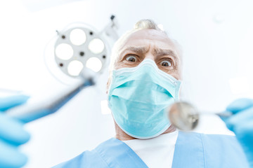 Excited professional dentist in medical mask holding dental tools and looking at camera