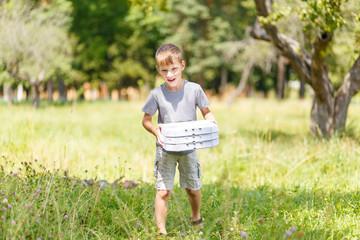 Small boy bringing three box of pizza for a picnic at the summer park