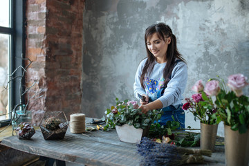 female  in gray blouse and jeans make a bouquet over gray background, putting roses in vase, flowers and vase on wood table, workplace