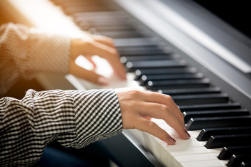 Close up of woman hands playing piano