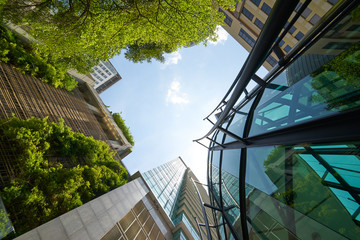 Low angle shot of modern glass buildings and green with clear sky background. Fototapete
