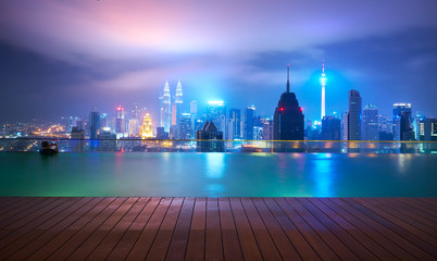 Fotomurales - After the rainy night, in the roof top of the swimming pool, visitors swim while enjoying beautiful city skyline view ,Kuala lumpur, Malaysia.