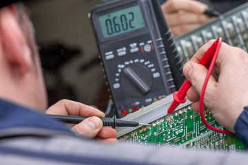 Checking circuit by Multimeter. Electrical engineer on during checking circuit board unit by Multimeter.