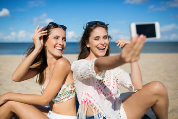 Pretty girls sitting on beach taking selfie laughing