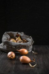 Burlap sack with onion on the wooden table. Selective focus