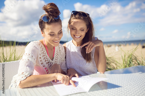 Two Happy Girls Sitting At Cafe Table On Beach Reading Menu