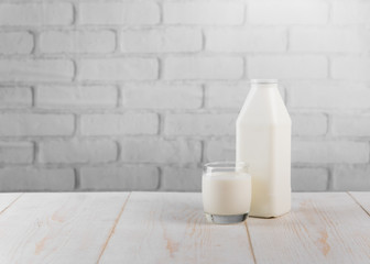 Fresh milk on wooden table against white brick wall