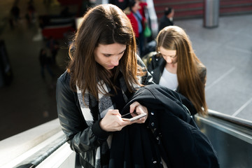 Women with phones on escalator