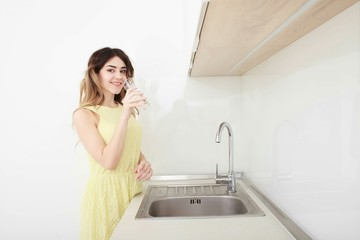 Beautiful young woman holds a glass with water on kitchen