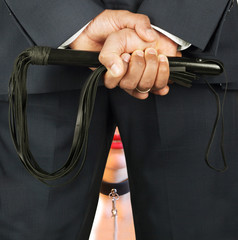 Master holding leather whip in front of his slave