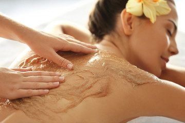 Young woman receiving scrub massage in spa salon