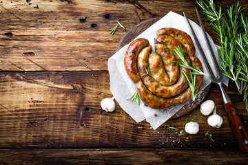 Grilled sausage on dark rustic wooden background, top view