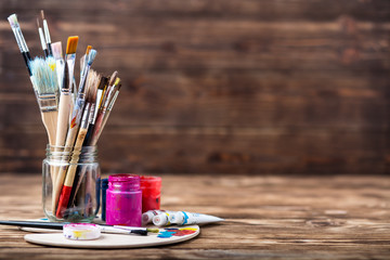 Artist's workshop. Top view of paintbrushes palette and acrylic paints with white canvas. Set of brushes and oil paints. Art picture with copy space and for add text.Items for children's creativity Wall mural