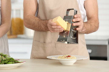 Young couple preparing pasta on kitchen table, closeup
