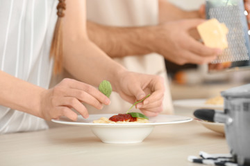 Woman hands decorating pasta on kitchen table