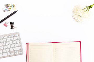 Desk in office with keyboard, pencil, colored paper clips, chrysanthemum flower and open the pink diary on a white background. Business concept.