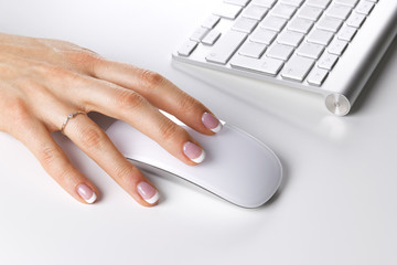 Closeup of businesswoman hand using wireless computer mouse and keyboard