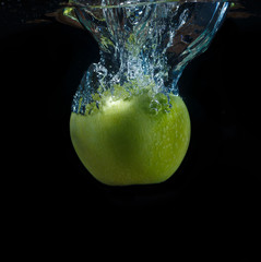 Printed roller blinds Splashing water Green apple with water splash on a black background