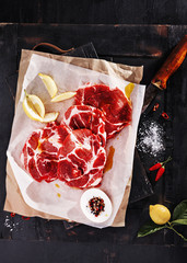 Raw fresh meat steak for grill with ingredients and knife on old black board.Top view.