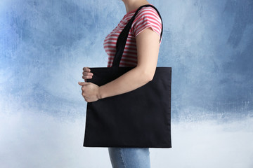 Young woman with shopping bag on color background