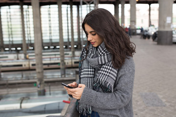 Woman with phone at train station