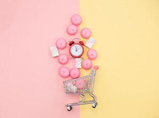 photo of marshmallows and alarm clock near shopping cart on the wonderful background in pop art style