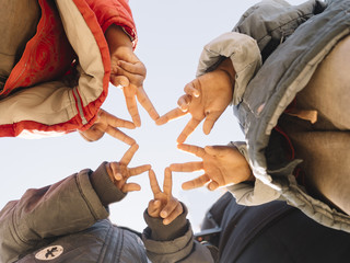 Low angle view of friends making star with fingers