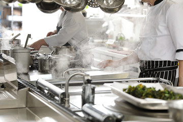 Foto op Canvas Koken Chef in hotel or restaurant kitchen cooking