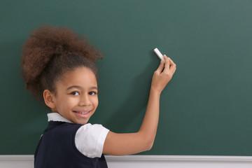 Cute African-American girl near blackboard