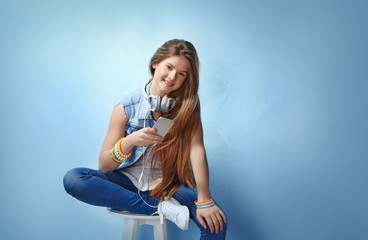 Pretty teenager girl posing on color background