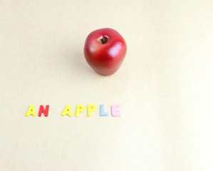 An red apple with alphabet on brown paper.