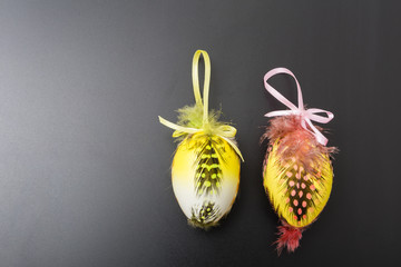 An easter egg painted and dressed in feathers