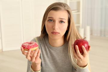 Beautiful young woman making choice between apple and doughnut