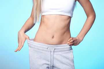 Diet concept. Young beautiful woman in big pants on light background