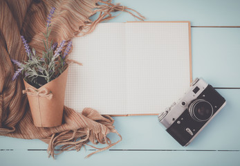 Top view image , open blank notebook, old camera on white wooden table