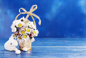 Vintage gold metal basket with daisy flower on a blue background for easter day with bunny. Copy space, selective focus.