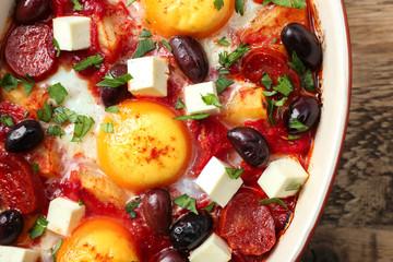 Baking dish with tasty Spanish baked eggs, closeup