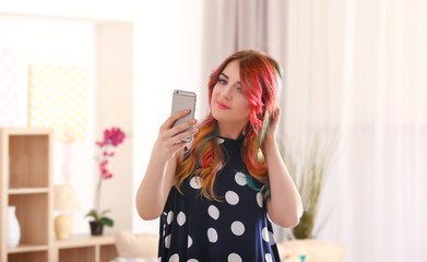 Young woman with colorful dyed hair making  selfie at home
