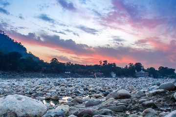 View of River Ganga and lots of stones after sunset with amazing dramatic sky. Rishikesh. India.