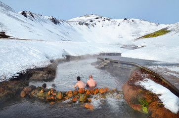 People sitting in Hot river in Iceland in winter snowy mountains