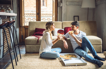 Cheerful couple eating pizza